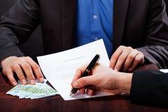Express cash loan. A closeup of a men signing an express cash loan agreement Royalty Free Stock Image