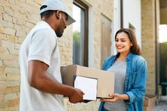 Express Delivery. Courier Delivering Package. Woman Receiving Parcel From Delivery Man Near Home. High Resolution royalty free stock image