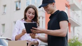 Express Delivery Service. Woman Receiving Package From Courier. Signing Delivering Document Outdoors stock video footage