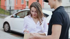 Express Delivery Service. Woman Receiving Package From Courier. Signing Delivering Document Outdoors stock video