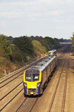 Express passenger service. TWYFORD, UK - OCTOBER 3: A FGW express 180 unit passes a suburban unit at speed as it passes Hare Hatch cutting on October 3, 2014 in Stock Images
