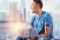 Positive delighted young man working at home. Express positivity. Dreamy male holding laptop and turning head while sitting against urban surrounding Royalty Free Stock Image