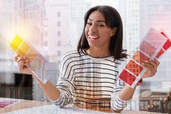 Delighted international engineer posing on camera. Express positivity. Young professional keeping smile on her face and showing colorful palettes while looking stock photo