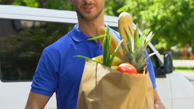Express service of delivery products from supermarket, courier holding out bag. Stock footage stock footage
