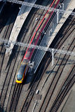 Express train arriving at a station. Bird's eye view of a train approaching a station, sidelit in the morning light Stock Photos