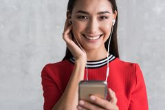 Cheerful stylish girl is enjoying her song. Express yourself. Portrait of happy young asian woman is touching her ear and holding mobile phone while listening to stock photography