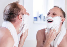 Expressed young man shaving near the mirror Royalty Free Stock Photos