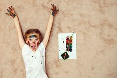 Expressief meisje in verven die bij vloer het gillen liggen royalty-vrije stock afbeeldingen