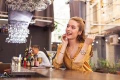 Expressieve jonge meisjeszitting bij de barteller en het kijken gelukkig stock foto