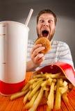 Expressieve mens die snel voedsel eet Royalty-vrije Stock Foto