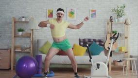 Expressieve te zware mens met een snor en glazen grappige dansende langzame mo stock video