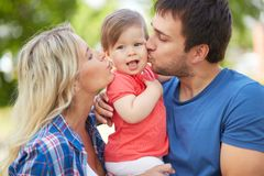 Expressing affection. Photo of affectionate parents kissing their small daughter Royalty Free Stock Images