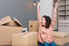 Expressing brightful true emotions, positivity of young pretty woman with short brunette curly hair on bed surround. Carton boxes in modern apartment. Enjoying stock image