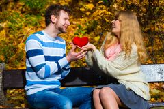 Romantic pair sit on bench in autumnal park. Expressing feelings and affection. Confess love with romantic gesture. Young couple sit on bench in park holding Royalty Free Stock Image