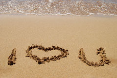 Expressing love. The words I love you written in the beach sand royalty free stock image
