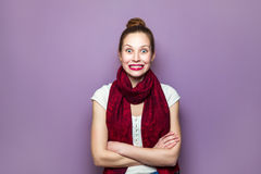 Expressing positive emotions, smile with big eyes and teeth. Surprised Woman. Young emotional beauty with collected hair and red scarf looking excited, crossed Royalty Free Stock Image