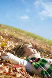 Expressing positivity. Blond girl resting on autumn leaves royalty free stock photos