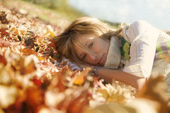 Expressing positivity. Blond girl resting on autumn leaves royalty free stock photography