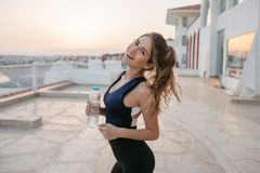 Expressing positivity, happiness of joyful young woman at training on seafront in early sunny morning. Attractive figure. Fashionable sportive woman, summer royalty free stock photography