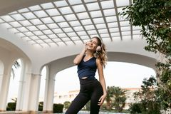 Expressing positivity of joyful pretty woman in sportswear by training smiling to camera on east architecture background. Listening to music through headphones royalty free stock images