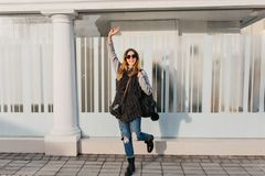 Expressing positivity, true brightful emotions of joyful fashinable girl on street in city. Amazing young woman in. Woolen sweater, sunglasses travelling with stock images