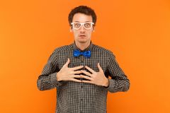Expressing professor looking at camera, holding heart and looking at camera with big eyes. Indoor, orange background stock photo