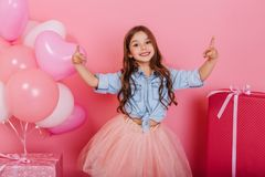 Expressing true positive emotions to camera of joyful happy kid suround balloons and presents  on pink