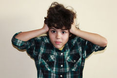 Expression. Studio portrait of a boy in colorful shirt with hands on his head Stock Photography