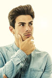 Expression of doubt or choice. Young man thinking. On white royalty free stock photos
