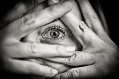 Scared girl covering her face with her hands and with her eyes on alert stock photo