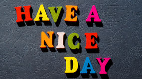 The expression `Have a nice day` made of colorful wooden letters on a dark table. Photo Royalty Free Stock Image