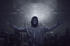Expression hooded man wearing mask with open arm. On digital modern city background Royalty Free Stock Image