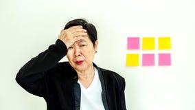 Expression malheureuse de femme supérieure asiatique d'affaires avec l'espace n de copie Photo stock