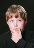 Expression pensante de garçon au-dessus de noir Photographie stock