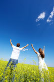 Expression of praise. Back view of young guy and girl looking at sky with raised arms in yellow meadow Royalty Free Stock Image