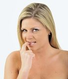 Expression Series - coy. Expression Series - beautiful blonde woman with hand to lip - sheepish or coy royalty free stock image