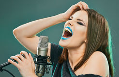 Expression woman singer portrait with microphone. Beautiful model with long hair posing at sound record studio royalty free stock photo
