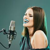 Expression woman singer portrait with microphone. Beautiful mod. El with long hair posing at sound record studio royalty free stock image