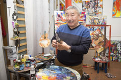 Expressionist artist in his art studio. Expressionist artist in the interior of his art studio among his paintings Stock Image