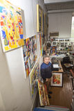 Expressionist artist in his art studio. Expressionist artist in the interior of his art studio among his paintings Royalty Free Stock Images