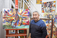 Expressionist artist in his art studio. Expressionist artist in the interior of his art studio among his paintings Stock Images