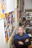 Expressionist artist in his art studio. Expressionist artist in the interior of his art studio among his paintings Stock Photography