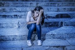 Expressionist edited portrait of young sad and depressed woman or teen girl sitting lonely at street staircase looking desperate a. Nd suffering problem in Royalty Free Stock Photo