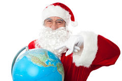Expressionistic Santa pointing at north pole. On globe. All on white background Stock Image