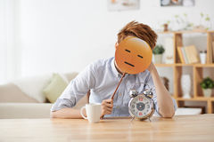 Expressionless face. Man sitting at the table with alarm clock and covering his face with emoji Royalty Free Stock Photos