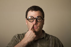 Expressionless picker. No expression at all a guy with glasses picks his nose Royalty Free Stock Photos
