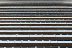 Expressionless, standardized modern architecture building. Contemporary modern building exterior of expressionless, standardized layers of windows and balconies Stock Photos