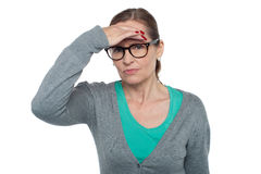 Expressionless woman looking at distance object. Isolated on white Stock Image