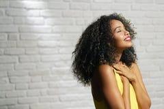 Expressions du visage de jeune femme de couleur sur le mur de briques images stock