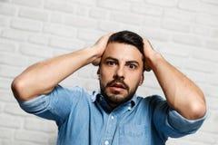 Expressions du visage de jeune homme de barbe sur le mur de briques photographie stock libre de droits